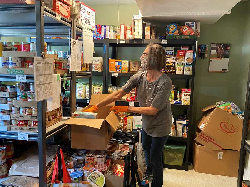 PMG PHOTO: HOLLY BARTHOLOMEW - Food Pantry volunteer Carol Feucht consults a list of food requested by a family as she prepares their box.