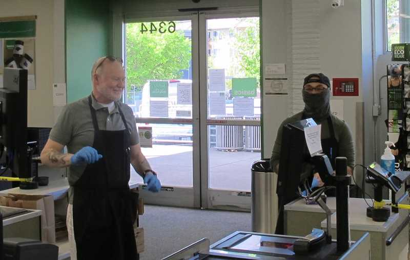 PHOTO BY; BILL GALLAGHER - Basics Market employees Dan MacLeod (l) and Eric Vaulte (r) making sure surfaces are sanitized at the Hillsdale store.