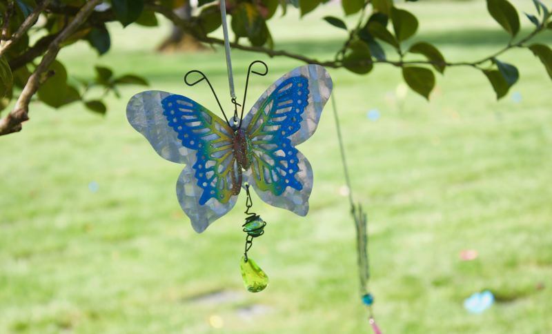 PMG PHOTO: CHRISTOPHER KEIZUR - Metal butterflies were placed in the trees around the childrens section of Greshams Forest Lawn Cemetery.