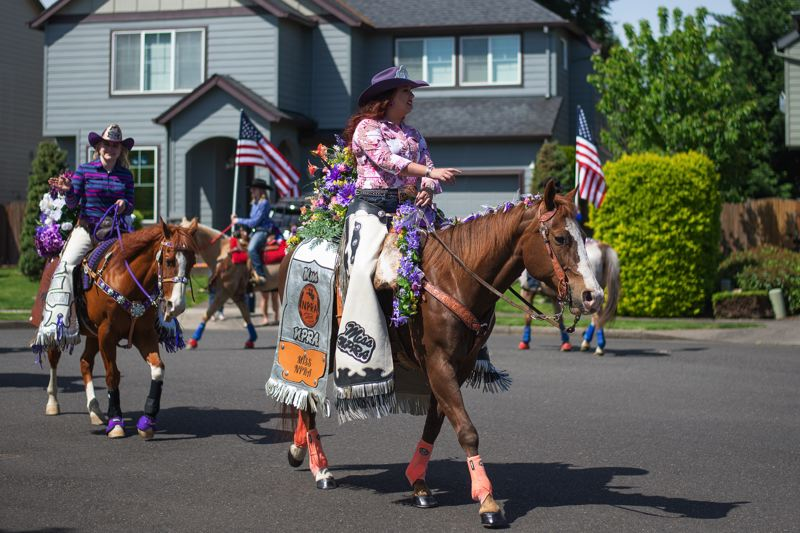 PMG PHOTO: ANNA DEL SAVIO - Nicole Rice, left, is a Scappoose resident and the Northwest Professional Rodeo Association's Miss NPRA for 2020 and 2021. Rice organized a rodeo parade through Scappoose on Saturday, May 9, to offer socially distanced entertainment as fairs and rodeos across the country are canceled due to COVID-19. 2020 Columbia County Fair and Rodeo Queen Jessica Lincoln follows behind.
