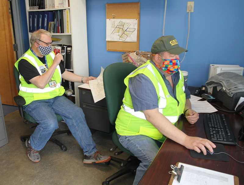 PMG PHOTO: JUSTIN MUCH - CERT volunteers Rob Mill, left, and Walt VanRheen work on coordinating a route for food box deliveries in Woodburn on Tuesday, April 21., Woodburn Independent - News