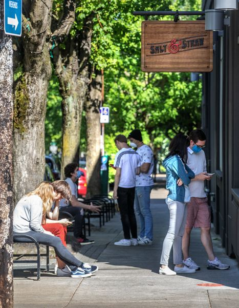 PMG: JONATHAN HOUSE - Salt & Straw customers often order on their smart phones in the street then wait a few minutes for their pints to be pushed out of the makeshift service hatch. This is the Northwest 23rd Avenue store in Portland on one of the first hot days in May.
