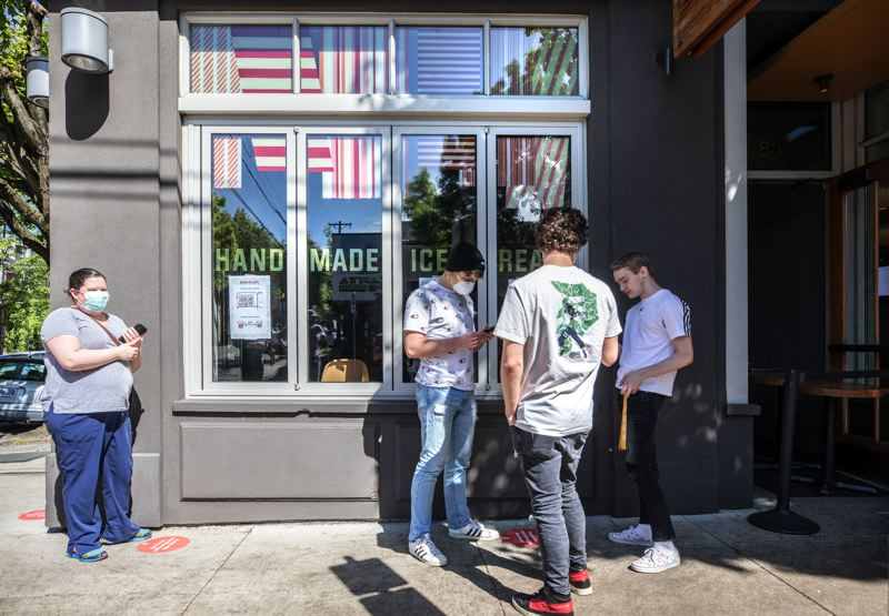 PMG: JONATHAN HOUSE - Customers outside the partially newly reopened Salt & Straw ice cream store on Northwest 23rd Avenue store in Portland on one of the first hot days in May. These men drove in from Scappoose for the experience.