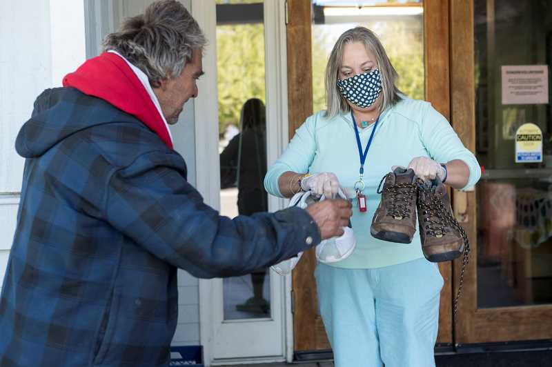 PMG PHOTO: JAIME VALDEZ - Good Neighbor Center Executive Director Renee Brouse gives David Kyle Dennis, who said he was hitchhiking to Maine, a pair of shoes Friday. Brouse said the COVID-19 pandemic has meant more demand for services to homeless families.
