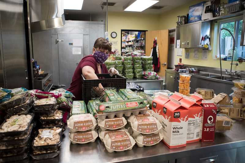 PMG PHOTO: JAIME VALDEZ - Traci Miller, a staff member at the Good Neighbor Center, sorts through food that was donated to the Tigard homeless shelter.