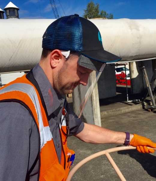 COURTESY PHOTO - WES Plant Operator Patrick Mahoney turns a valve while wearing a shield.
