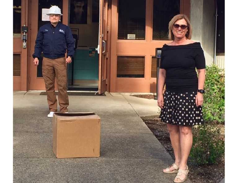 COURTESY PHOTO - WES Operations Manager Greg Eyerly receives a box of face shields from Lori Olund, president of Miles Fiberglass.