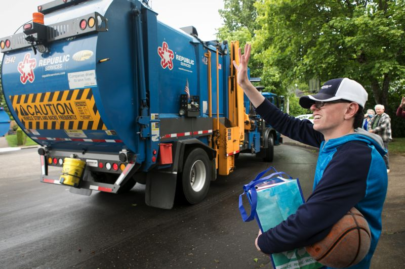 PMG PHOTO: JAIME VALDEZ - Harrison Halstead,14, waves to the men operating Republic Services' garbage trucks on Tuesday, May 12, 2020 in front of his home in Wilsonville. The waste & recycling service based in Wilsonville surprised Halstead with a drive-by with garbage trucks. Halstead is a big fan of Republic Services.