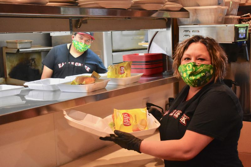 PMG PHOTO: EMILY LINDSTRAND - Staff at the Eagle Creek Saloon prepare food for Meals on Wheels recipients.