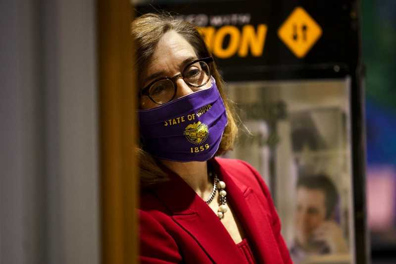 PMG PHOTO: JAIME VALDEZ - Gov. Kate Brown, masked for social distancing, begins a Thursday, May 7, press conference in Portland. , Portland Tribune - News Gov. Kate Brown addresses questions about how and when the state could emerge from the umbra of the coronavirus quarantine.  Governor says Oregon could reopen under 3-phase plan