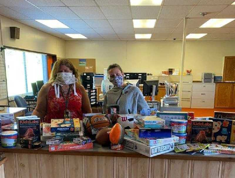 COURTESY PHOTO - Katrina Raasch, CSD executive secretary, receives toys, games, puzzles and a check from Kendall Schumaker with the nonprofit Building Blocks 4 Kids. The toys will go to help the kids served through the school's lunch program.