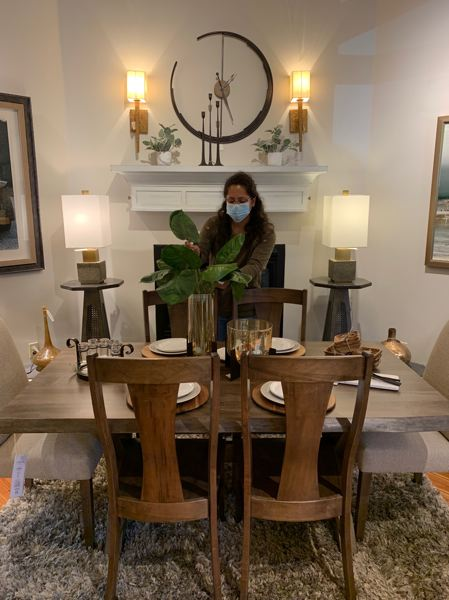 COURTESY PHOTO: CELEBRATE ME HOME - McKenna Dover puts the finishing touches on a display at Celebrate Me Home in Troutdale. The store plans to open May 26.