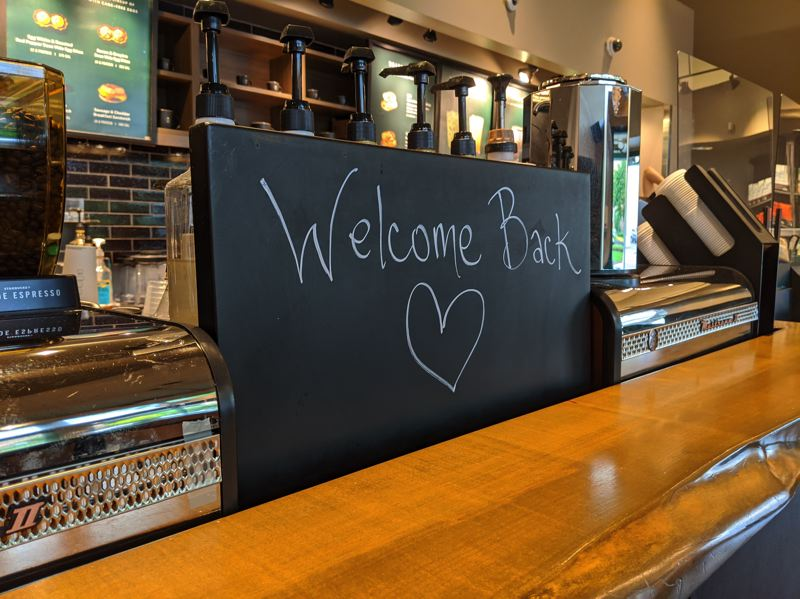 PMG: JOSEPH GALLIVAN - Starbucks at 1012 NW 21st Ave was open Friday. Customers could go inside, order at the counter and wait for their drink to be passed to them under a plastic barrier. They could not sit down or drink inside.