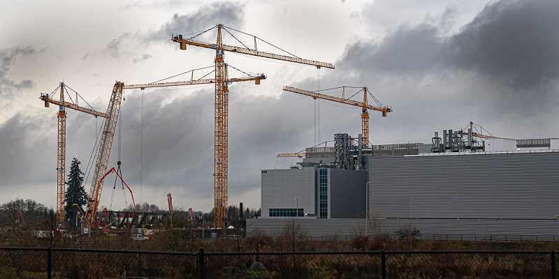 TIM HERMAN/INTEL CORPORATION - Cranes at Intel's Ronler Acres where the next big fab is going up. As Oregon issued 'Stay Home' orders during the COVID-19 pandemic, Intel kept many of its employees working, and faced OSHA complaints for it.