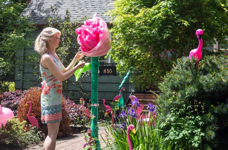 PMG PHOTO: JONATHAN HOUSE - Angela Daniels fixes up a rose decoration in her front yard in anticipation of the Rose Festival Porch Parade.