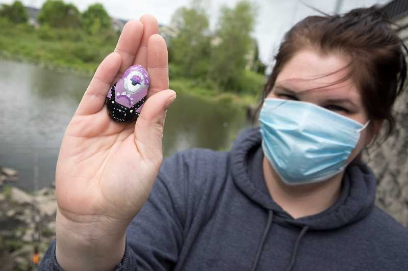 PMG PHOTO: JAIME VALDEZ - Taryn Fullmer displays the rocks she paints and distributes along the Rock Creek Trail next to Bethany Pond. Fullmer said she started the project as a way to find something for her son to do while cooped inside because of the coronavirus pandemic.