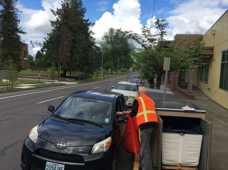 PMG PHOTO: JOHN SCHRAG - A Washington County elections worker gathers ballots as a line of cars wait on Pacific Avenue in Forest Grove Tuesday afternoon, May 19.
