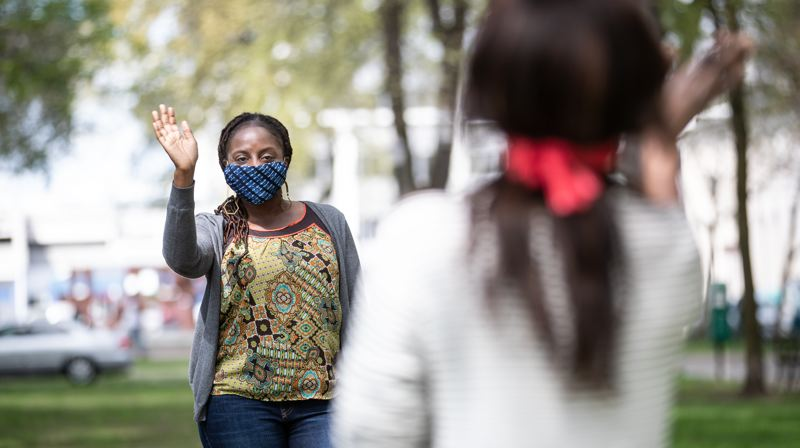 MULTNOMAH COUNTY PHOTO: MOTOYA NAKAMURA - Local residents in Multnomah County greet each other while wearing face masks last month.