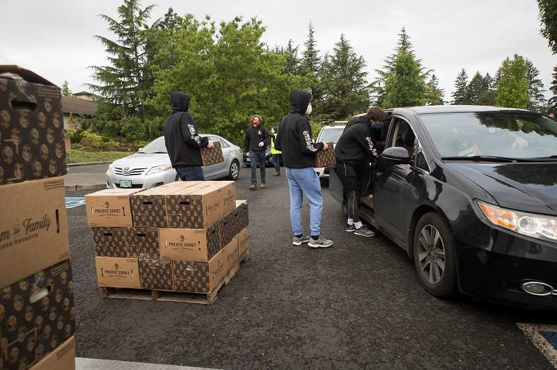 PMG PHOTO: JAIME VALDEZ - Scott Taylor, 20, Jack Shelby, 22, Jamie Taylor,19, and Will Shelby, 19, all cousins load boxes of food for a person at Resurrection Catholic Parish in West Linn.