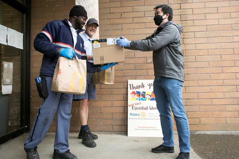 PMG PHOTO: JAIME VALDEZ - Mike Wu, right, the incoming president of West Linn Rotary Club, hands over breakfast from McDonald's to West Linn Post office workers' Simon Ajayi, left, and Kirk Bartram on Tuesday, May 12, as a thank you to essential workers.