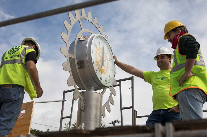 PMG PHOTO: JAIME VALDEZ - Robert Musante of Columbia Associates, left, Brandon Petersen of the Tigard Breakfast Rotary Club, and John Flynn, principal architect with RESOLVE Architecture and Planning, install the Rotary wheel on the new Tigard Rotary Plaza clock Sunday.