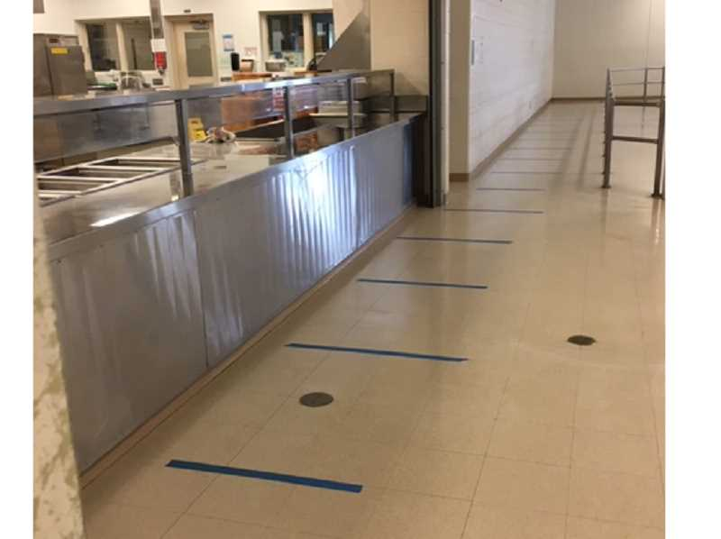 COURTESY PHOTO - Lines are taped on the floor of the dining hall at Deer Ridge Correctional Institution to show inmates how far apart they must stand as they go through the cafeteria line.