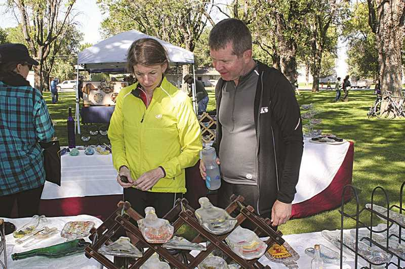 HOLLY M. GILL - Denise and John Patridge, of Portland, check out a booth at the Saturday Market at Sahalee Park, during Cycle Oregon's three-day, two-night visit.