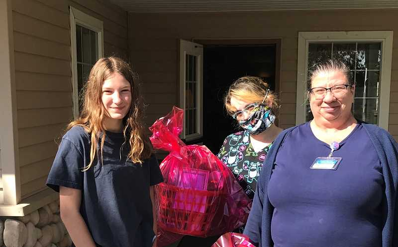 COURTESY PHOTO - Breanna Lacey, left, her mother, Stacy Lacey, center, and Rosa Carver, right, of East Cascade Retirement Community in Madras, deliver care packages assembled by Breanna and Stacy. Each included a piece of original artwork by 13-year-old Breanna.