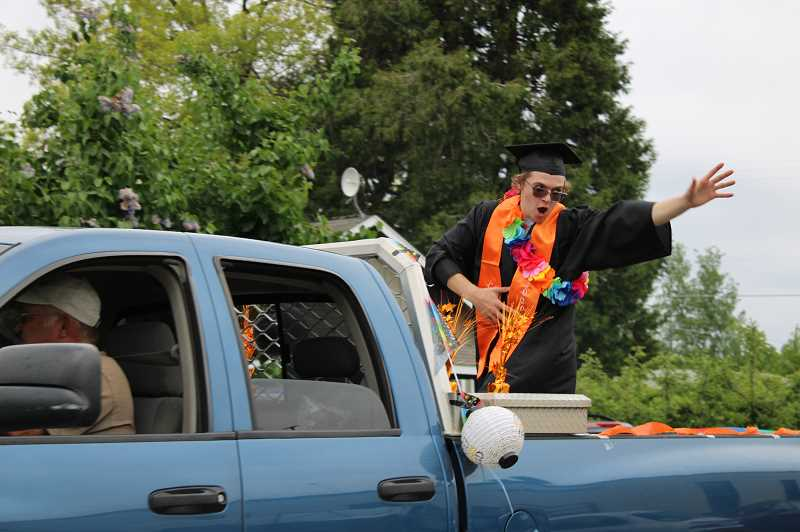TERESA JACKSON/MADRAS PIONEER - Culver High School graduate Tyson Ebersole waves to people lining the streets to ceelbrate the calss of 2020 in Culver Saturday, 16.