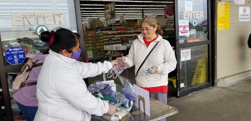 COURTESY OF PAM BRIDGEHOUSE - Lutheran Latino Ministries Deaconess Marta Luna recruited volunteers Natali Alfaro, Erick Velazquez and Obdulia Chavez to hand out masks at Woodburns Mega Foods on Wednesday, May 20.