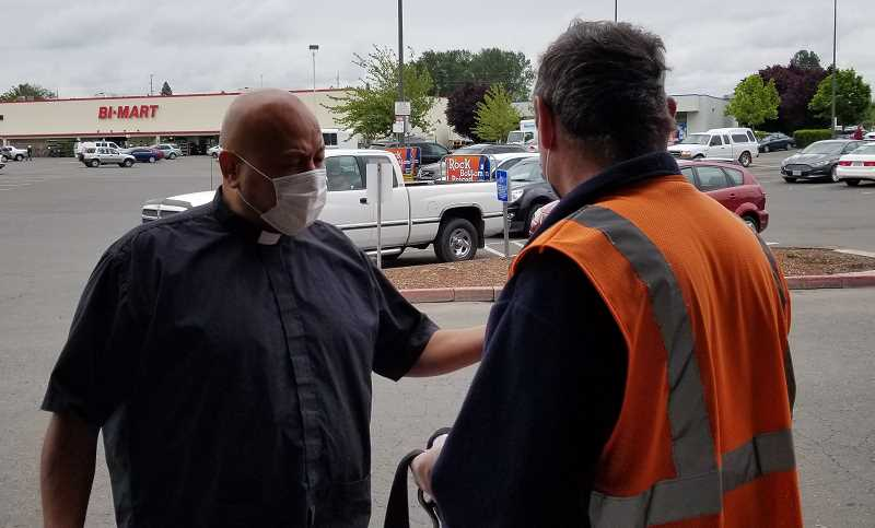 COURTESY OF PAM BRIDGEHOUSE - Pastor Zabdi Lopez of Hope Lutheran Church in Woodburn helps hand out safety masks at Mega Foods on Wednesday, May 20.