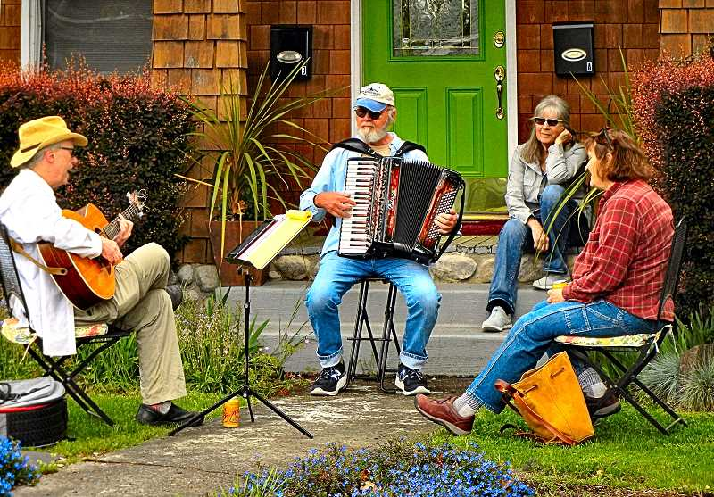 ELIZABETH USSHER GROFF - An informal group local professionals whimsically called the Social Distance Band plays on the front porch of musician Les Zigethy (center, with accordion) - with harmonizing by Dale Jones (left) and Ann Heyen (right). Barbara Zigethy was their audience, as the photo was taken. Their bi-weekly front-yeard concerts are a good isolation outlet.
