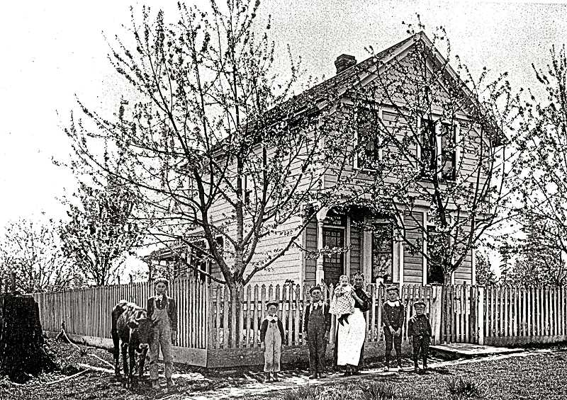 COURTESY OF JOAN & FRED COATES  - This photo from about 1890 shows Anna Taggesell holding the latest of her eventual seven boys (her daughter Anna was absent). The original photo identifies Carl (with the calf), Albert, Arthur, Rudy, Herbert, and Walter. They are standing in front of their home at 1514 S.E. Henry Street, built by their parents in 1888. Note the original level of the land before the public streets were graded.