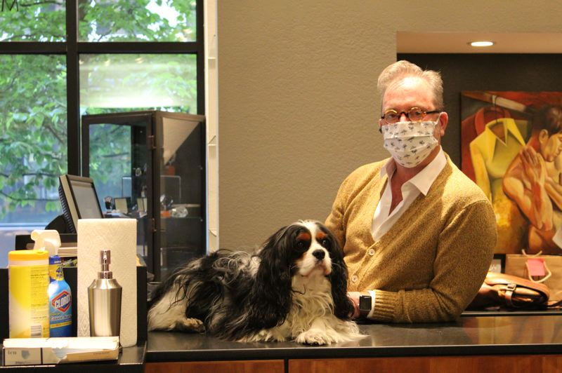 PMG:  HELENA GALLIVAN - Michael Allen Fredrickson, owner of Michael Allen's Clothier at 811 S.W. Morrison St., says most of his business is custom tailoring which requires measuring customers at close quarters. Regular customers have been in and shown their support: on the first day he reopened he sold 40 designer, cloth, face masks at $120 a piece. His dog is called Mr. Spencer.