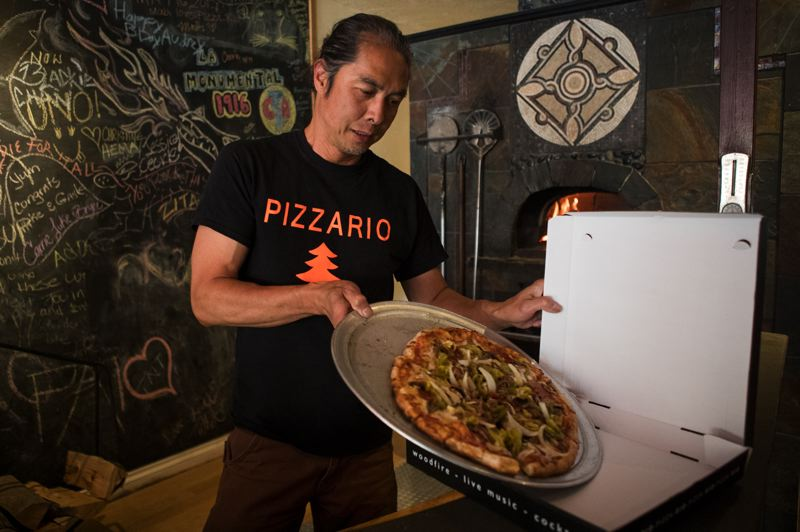 PMG PHOTO: JAIME VALDEZ - Mike Soto, owner of Pizzario, boxes up a pizza for a customer in Hillsboro.