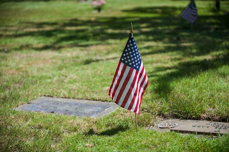 PMG FILE PHOTO: JON HOUSE - A flag flies over the headstone of a veteran in this 2016 file photo at Winona Cemetery.