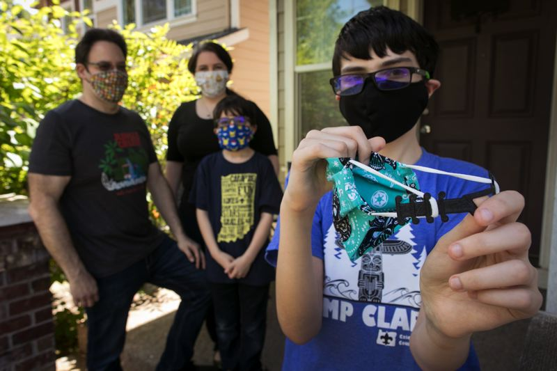 PMG PHOTO: JAIME VALDEZ - Joey, 13, a seventh grader at Summit Learning Charter, holds an ear saver for a face mask with his left hand that he and his family make at home from 3D printers. Behind Joey are his parents, David and Corey, and his younger brother, Charlie, 11, a fifth grader at Boeckman Creek Primary School.
