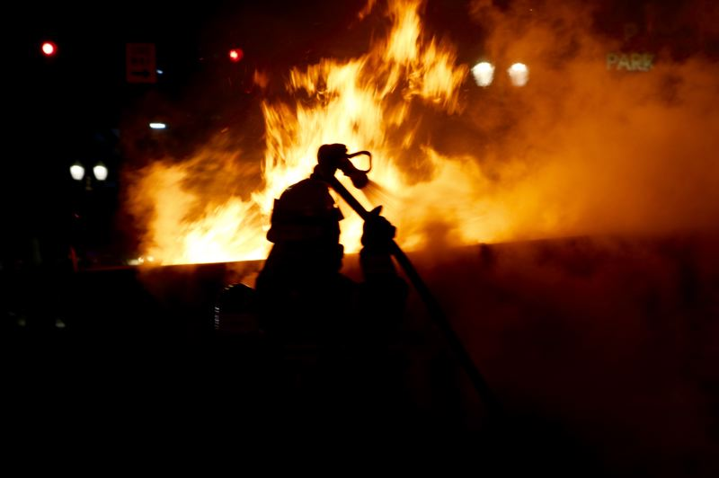 PMG PHOTO: ZANE SPARLING - A Portland Fire & Rescue firefighter put out a dumpster blaze in the street during a downtown riot on the night of Friday, May 29.