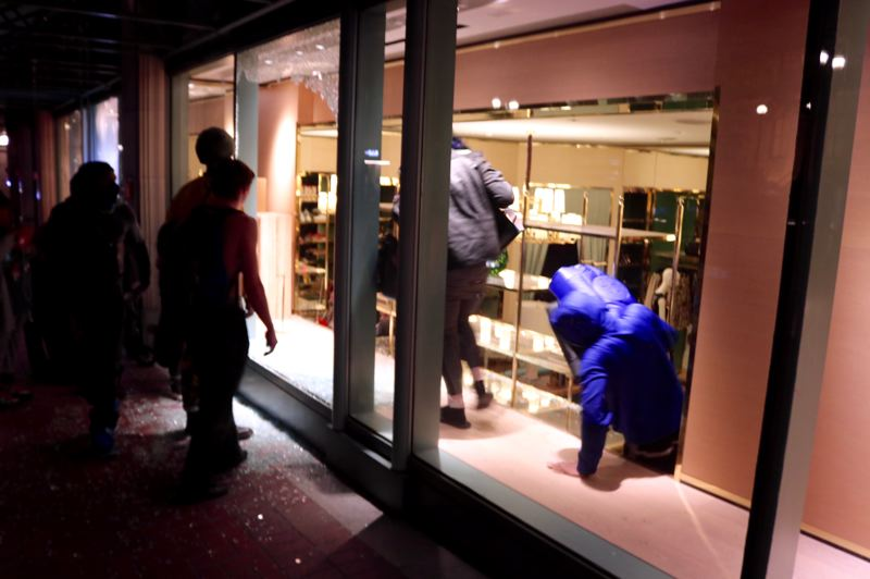PMG PHOTO: ZANE SPARLING - Looters scrambled out of a clothing store at Pioneer Place Mall during a riot in Portland on Friday, May 29.
