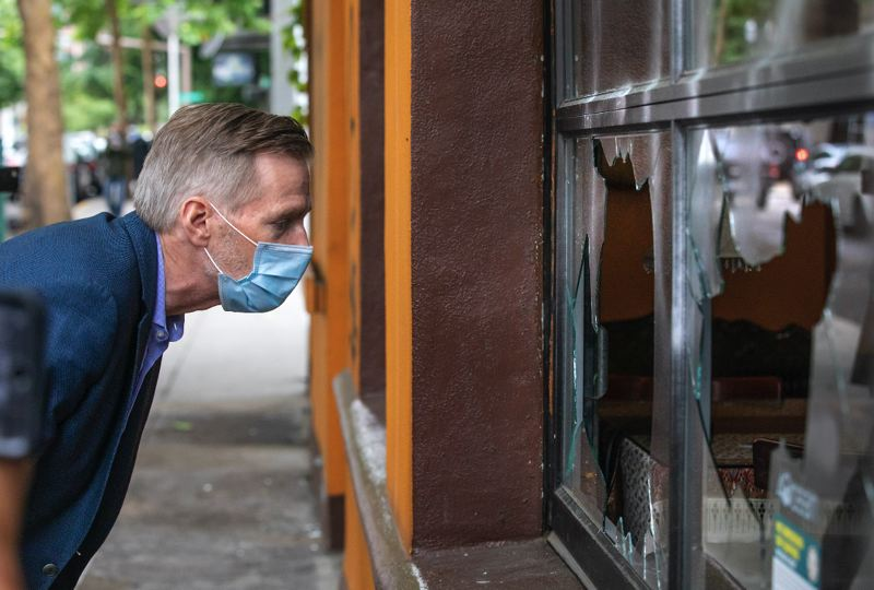 PMG PHOTO: JONATHAN HOUSE - Portland Mayor Ted Wheeler peers through broken window panes at a downtown establishment on Saturday, May 30.
