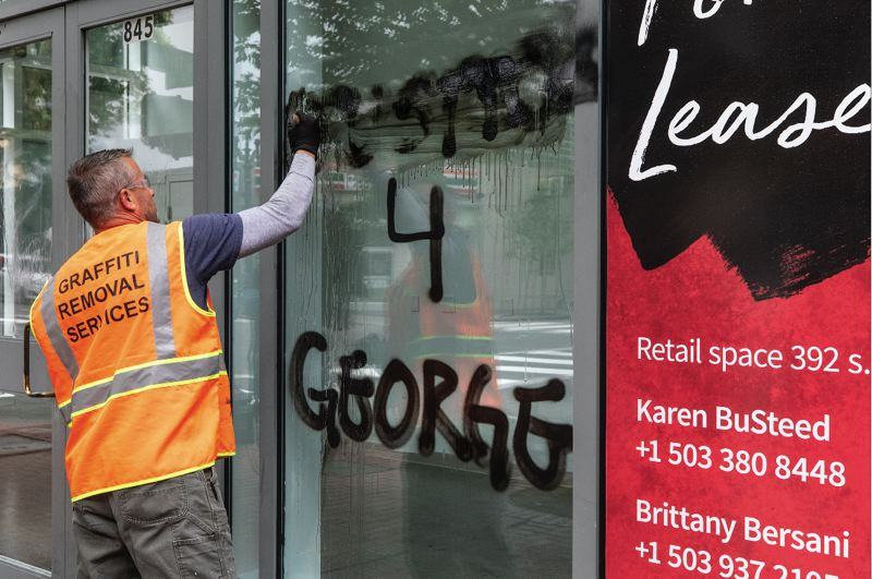 PMG PHOTO: JONATHAN HOUSE - A worker attempted to removal graffiti from a storefront in downtown Portland on Saturday, May 30.