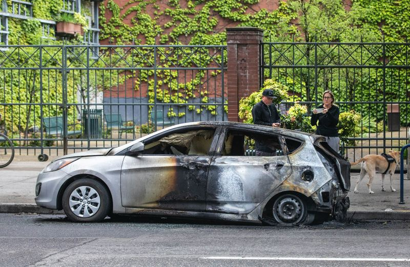PMG PHOTO: JONATHAN HOUSE - Passersby took photos of a burnt-out car that was destroyed during a downtown Portland riot.