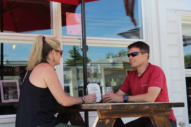 PMG PHOTO: HOLLY BARTHOLOMEW - Dan and Raandi Otto enjoy drinks outside the newly re-opened Willamette Ale and Cider House.