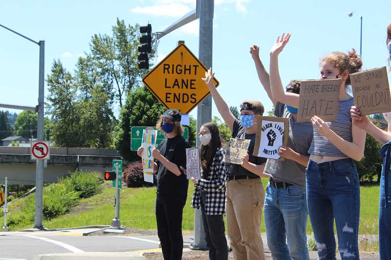 PMG PHOTO: HOLLY BARTHOLOMEW - West Linn students protest Monday, June 1 at the I-205 onramp at 10th Street and Salamo Road.