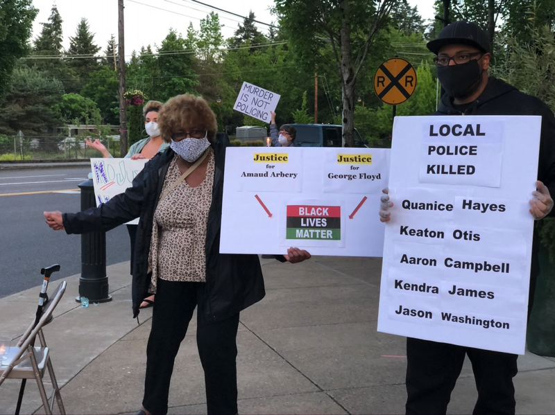 COURTESY PHOTO: ALANA KENT - Community members held signs and lit candles during a peaceful vigil in downtown Lake Oswego May 31.