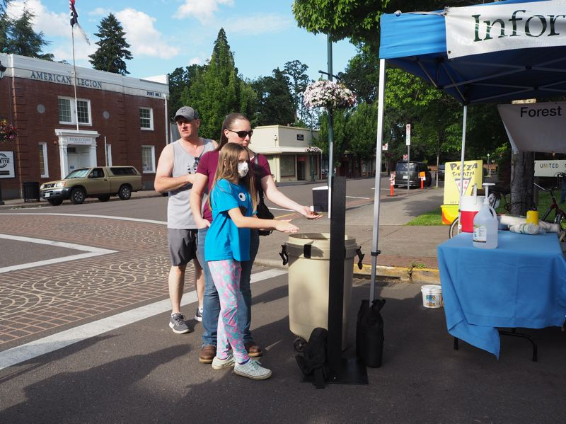 PMG PHOTO: MAX EGENER - Market-goers at the farmers market in Forest Grove use hand sanitizer at the entrance of the market on its opening day Wednesday, June 3.