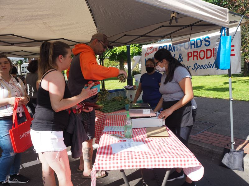 PMG PHOTO: MAX EGENER - Justin Dale and Deana Madrid purchase produce from the Crawford's Nursery and Produce farm stand at the farmers market in Forest Grove on Wednesday, June 3.