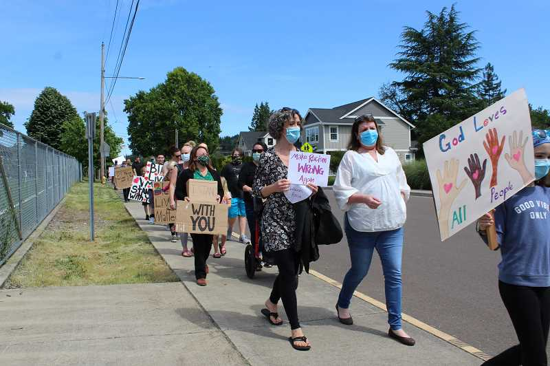 PMG PHOTO: HOLLY BARTHOLOMEW - Protestors walk around Willamette Primary School.