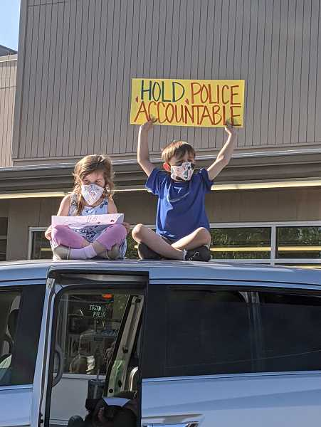 PMG PHOTO: COURTNEY VAUGHN - Vivian, 4, and Grayson, 6, hold a sign atop a van in Southwest Portland's Multnomah Village neighborhood Wednesday, June 3, during a demonstration against police brutality. The family-friendly event saw many adults and young people protesting for the first time.