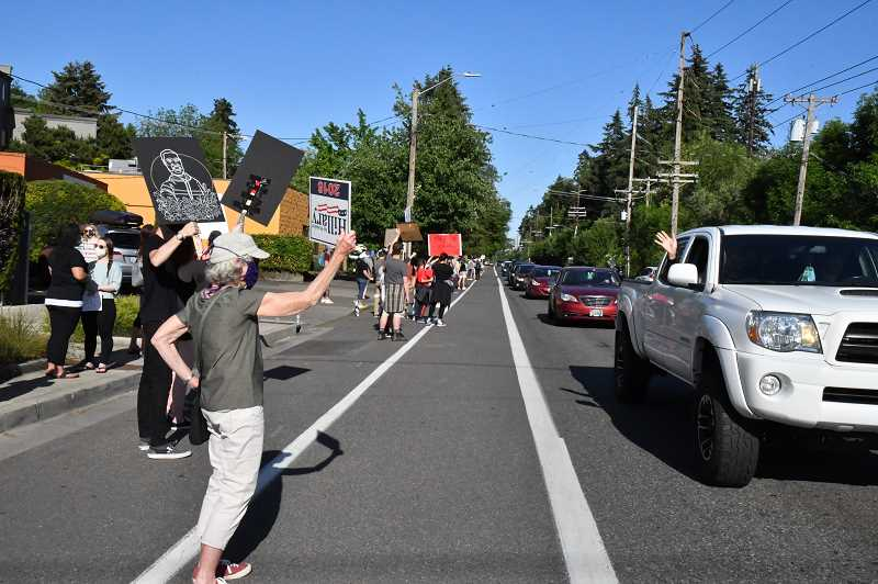 PHOTO: MARK JANES - Drivers honk and wave at Southwest Portland residents gathering along Multnomah Boulevard Wednesday, June 3, for a demonstration against police brutality.
